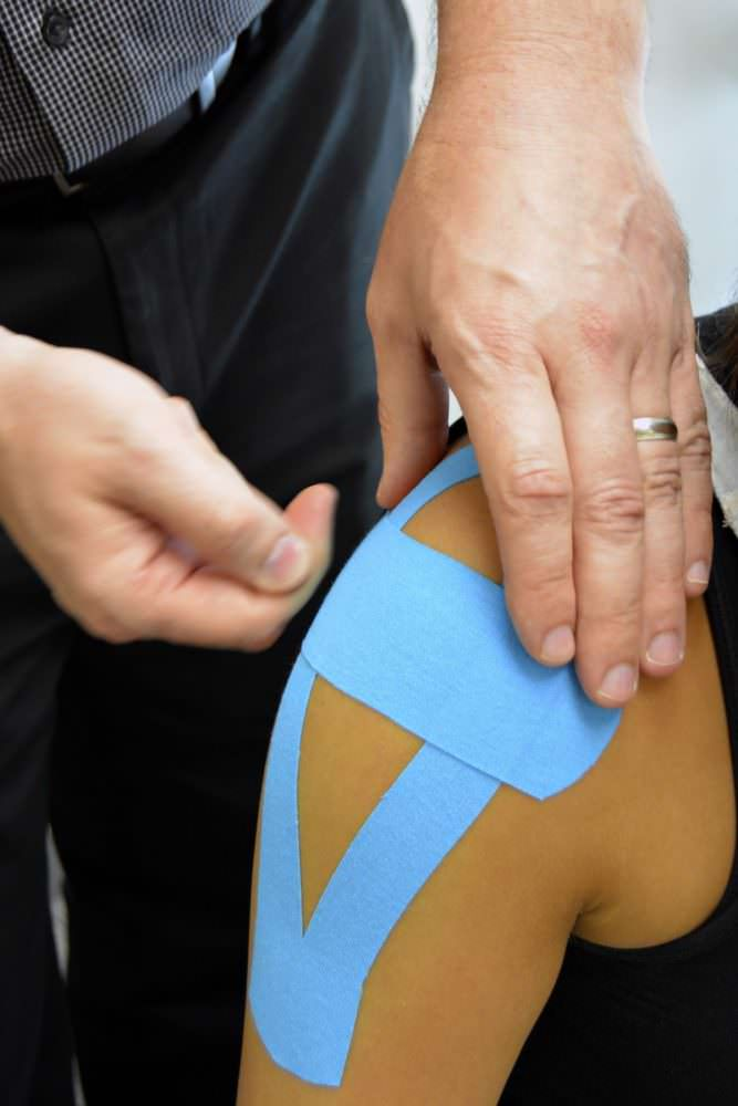 image of Dr French applying Kinesio tape for the shoulder